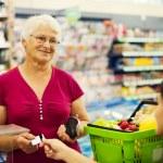Senior woman at supermarket — Stock Photo #21915761