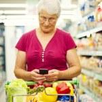 Senior woman at supermarket — Stock Photo #21915779