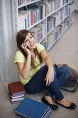 Student on the phone in library — Stock Photo