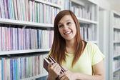 Student meisje lachen in de bibliotheek — Stockfoto