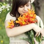 Woman enjoying the fragrance of flowers — Stock Photo