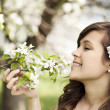 Woman enjoying the fragrance of flowers — Stock Photo #21951827