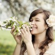 Woman enjoying the fragrance of flowers — Stock Photo #21952307