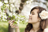 Woman enjoying the fragrance of flowers — Stock Photo