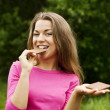 Young woman eating chocolate in forest — Stock Photo #21961217