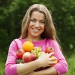 Young woman holding fruits and vegetables — Stock fotografie
