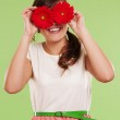 Smiling woman covering her eyes with two flowers — Stock Photo #21962631