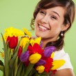 Portrait of a smiling woman with colorful flowers - Stock Photo