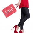 Woman holding shopping bag with Sale word on it — Stock Photo