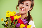 Happy young woman with flowers — Stock Photo