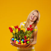 Happy woman holding basket with spring flower and easter eggs — Stock Photo