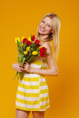 Young woman wearing in sundress with bouquet of tulips — Stock Photo