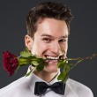 Man with a red rose in mouth — Stock Photo