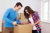 Loving couple packing boxes — Stock Photo