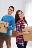 Happy couple carrying boxes in their new home — Stock Photo