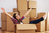 Cheerful woman sitting in a cardboard box — Stock Photo