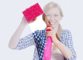 Young woman standing behind window and washing it — Stock Photo