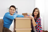 Portrait of young couple with moving boxes — Stock Photo