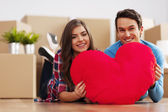 Young couple holding a heart shape in their new apartment — Stock Photo
