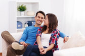 Loving couple sitting in living room — Stock Photo