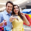 Beautiful couple showing credit card — Stock Photo