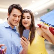 Smiling couple checking something on the mobile phone — Stock Photo #25415467