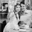 Happy couple in cafe holding digital tablet  — Stock Photo