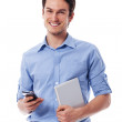 Happy man holding mobile phone and digital tablet — Stock Photo #25415751