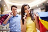 Mujer joven enfoque con tarjeta de crédito y bolsas de compras — Foto de Stock