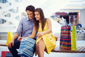Happy couple peeking into shopping bag — Stock Photo