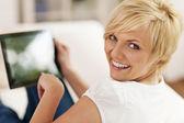 Lächelnde frau mit digitalen tablet zu hause — Stockfoto