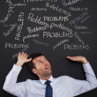 Businessman bending under stack of problems — Stock Photo #26981909