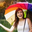 Surprised woman with umbrella during summer rain — Stock Photo