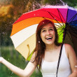 Surprised woman with umbrella during summer rain — Stock Photo #27343901