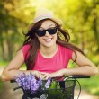 Portrait of smiling woman riding bicycle in park — Stock Photo #27343921