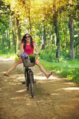 Happy woman enjoying a cycle ride in forest — Stock Photo