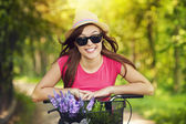 Portrait of smiling woman riding bicycle in park — Stock Photo