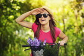 Happy woman with bike watching something — Stock Photo