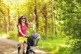 Beautiful woman waving to someone during cycling — Stock Photo