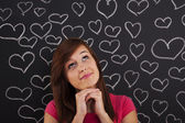 Woman looking up lovingly with hearts drawn on blackboard — Stock Photo