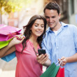 Young couple with shopping bag using mobile phone  — Photo