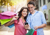 Young couple with shopping bag using mobile phone — Stock Photo
