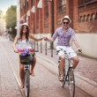 Happy young couple holding hands and riding on bike — Stock Photo