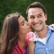 Young woman kissing her boyfriend on the cheek — Stockfoto