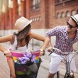 Happy couple chasing on bike in the street — Stock Photo #28680919