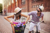 Happy couple chasing on bike in the street — Stock Photo
