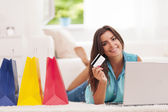 Beautiful woman paying by credit card for shopping at home — Stock Photo