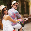 Happy couple riding bicycle in city street — Stock Photo #28852171