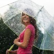 Young woman standing in summer rain with umbrella  — Foto de Stock