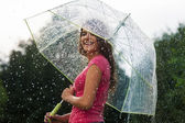 Young woman standing in summer rain with umbrella — Stock Photo